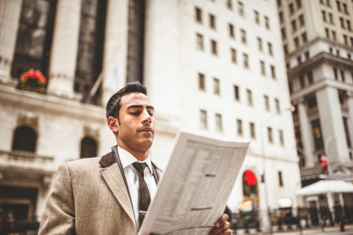 463173681-business-man-reading-a-newspaper-on-wall-gettyimages