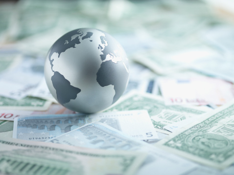 96502248-metal-globe-resting-on-paper-currency-gettyimages