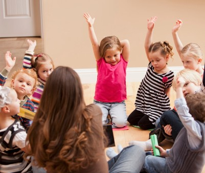 149261424-children-sitting-on-floor-and-raising-hands-gettyimages
