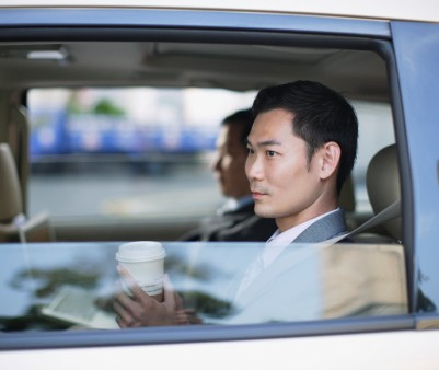 79365300-two-businesspeople-in-car-with-coffee-cups-gettyimages