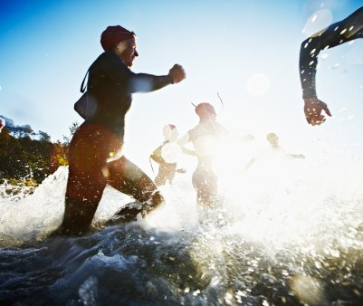 130905244-group-of-triathletes-running-into-water-at-gettyimages