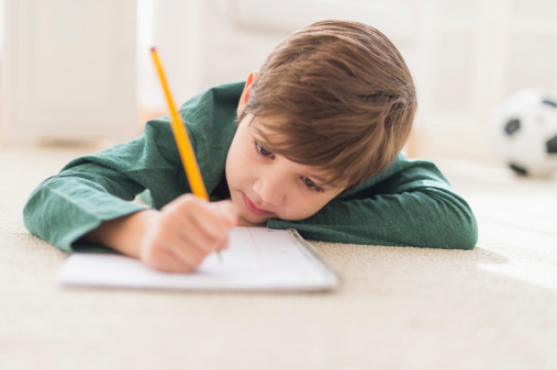 487703851-hispanic-boy-doing-homework-on-floor-gettyimages