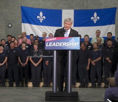 Le chef conservateur en campagne électorale lundi matin, le 3 août, dans l'usine Spectra Premium Industries de Laval. Les employés de l'usine se sont fait demander par leur patron de poser derrière Stephen Harper. (crédit photo: REUTERS/Christinne Muschi)