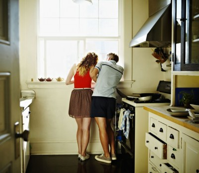 Couple standing looking out kitchen window