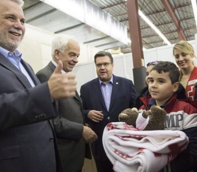 Philippe Couillard, John McCallum, Denis Coderre et Mélanie Joly accueillent des réfugiés syriens à Montréal. (Photo: Paul Chiasson/La Presse Canadienne)