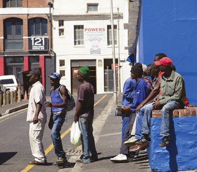 DPA9FN Black Men waiting on Strand Street Corner for Work Opportunities from Passersby - Cape Town - South Africa