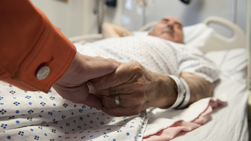 This senior citizen gets comfort from his daughter as she holds his hand before surgery (that will later reveal cancer). (Photo: iStockPhoto)