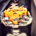 Skeleton's hands holding bowl of Halloween candies